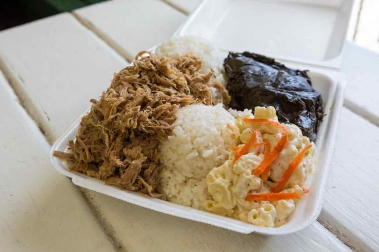 One of the best things to eat in Hawaii is a Hawaiian plate lunch. Image of a takeout box with kalua pork, lau lau, macaroni salad, and rice.