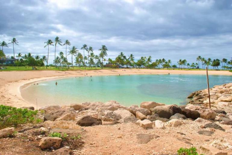 Ko Olina Beach is one of the best beaches on Oahu with kids. Image of a small lagoon with palm trees in the background.