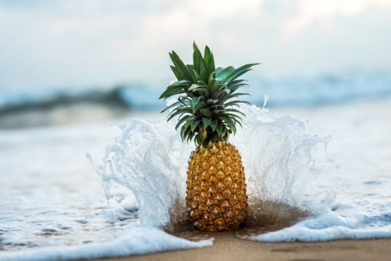 Planning a trip to Maui? One of the best pineapples in Hawaii is Maui Gold Pineapple. Image of a pineapple on the beach with waves crashing.