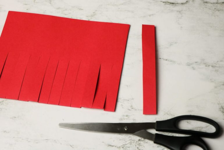 Cut a complete strip to use as your Chinese paper lantern craft handle. Image of red cardstock with slits cut into it.
