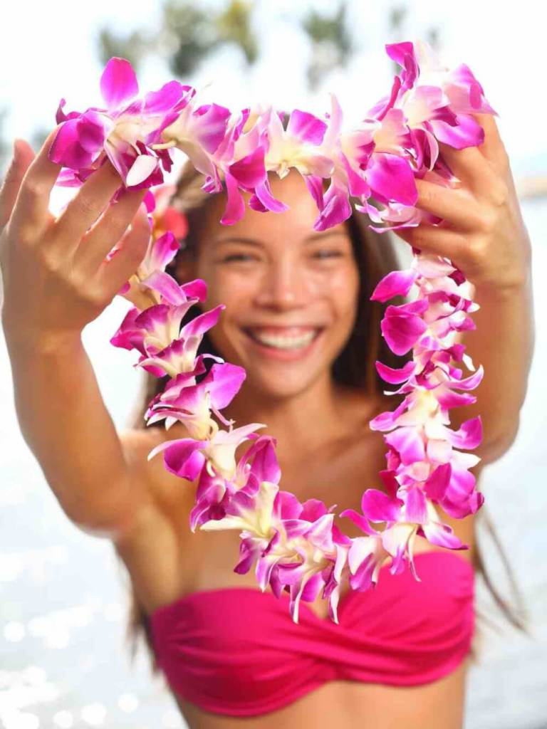 Image of Hawaii woman showing flower lei garland of pink orchids. Beautiful smiling mixed race woman in bikini on beach giving a welcoming Lei on the hawaiian island Big Island.