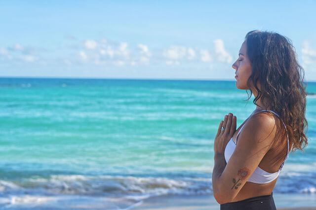 Image of a woman meditating while doing Maui beach yoga.