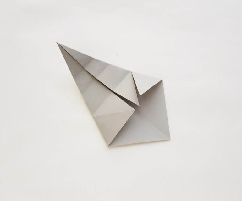See how to make a paper shark craft. Image of a grey paper folded and unfolded a bunch of times.