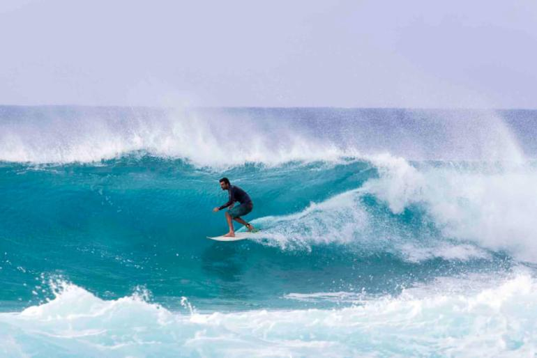 Surfing is one of the official state sports of Hawaii. Image of a surfer riding barrels of the Banzai Pipeline, a very popular pro-surf spot at the Northshore region of O'ahu.
