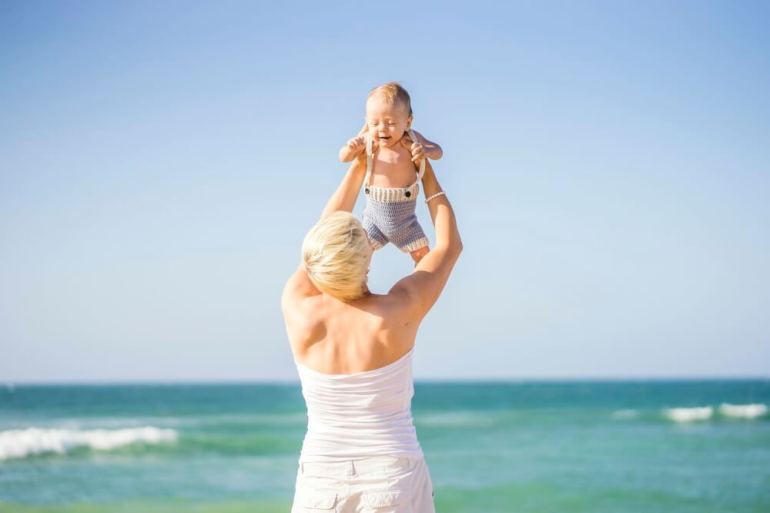 Find out why you should visit Hawaii with a baby. Image of attractive blond mother playing with 4 months old baby boy on the beach