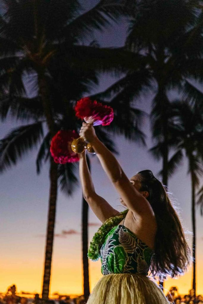 One of the best things to do on Oahu with kids is check out a free hula show. Image of a hula dancer using feather gourd rattles as she dances at sunset.