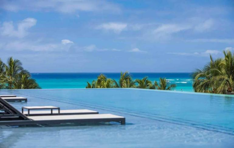 The Alohilani Resort & Spa is one of the best kid friendly hotels on Oahu. Image of an infinity pool with lounge chairs in the water and a view of the ocean.