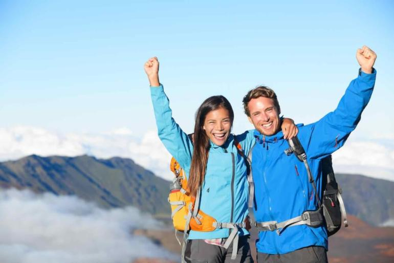 Hikers - people hiking cheering on summit top with view on volcano. Don't forget to wear warm clothes when hiking Haleakala National Park. Image of a hiker couple looking at beautiful landscape of mountain volcanoes at Haleakala on Maui.