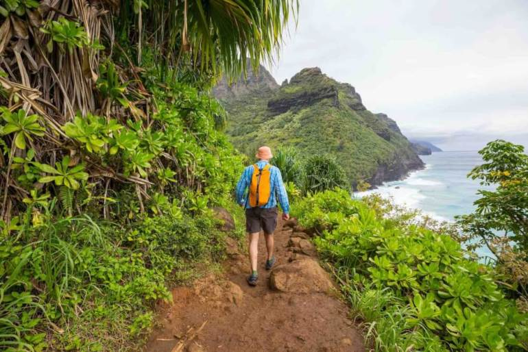 Make sure to pack all the essentials when hiking on Kauai. Image of a man wearing an orange backpack hiking on Kauai