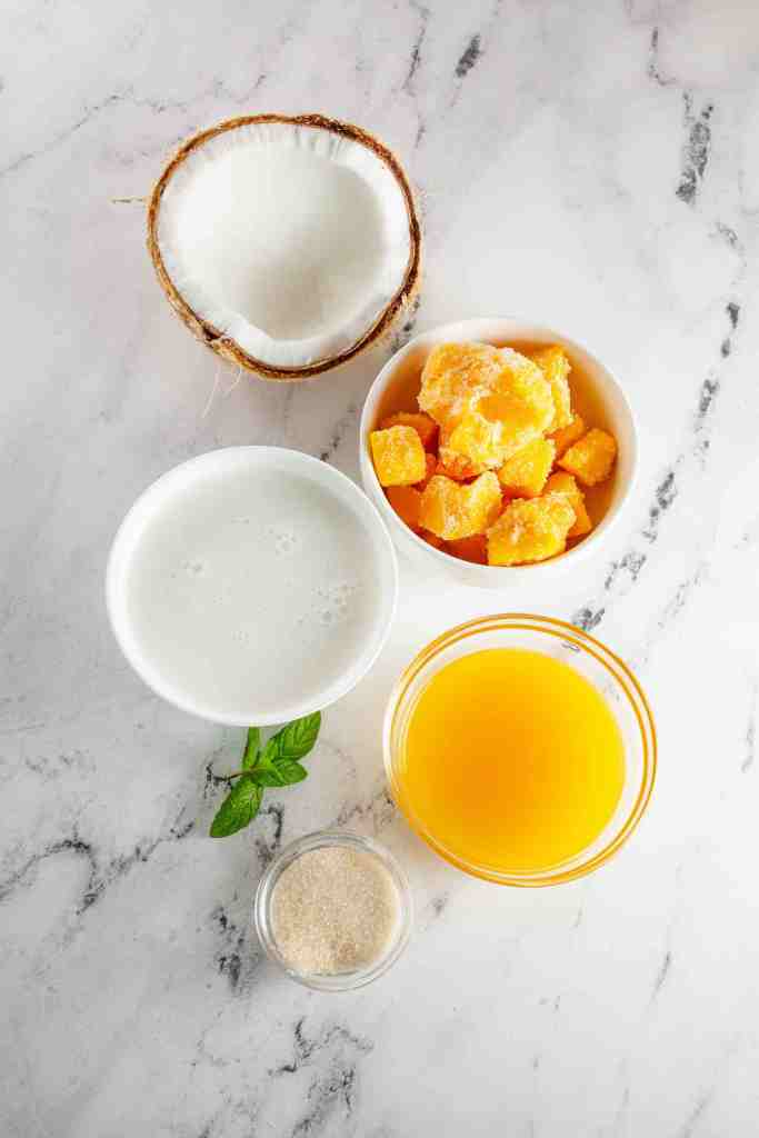 These are the ingredients to make mango coconut popsicles. Image of mango juice, frozen mango chunks, sugar, and coconut milk.