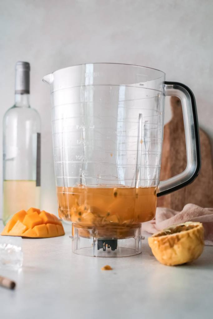To make a wine slushy, pour all the ingredients into the blender. Image of a blender with fresh mango, passion fruit, wine, and honey inside.