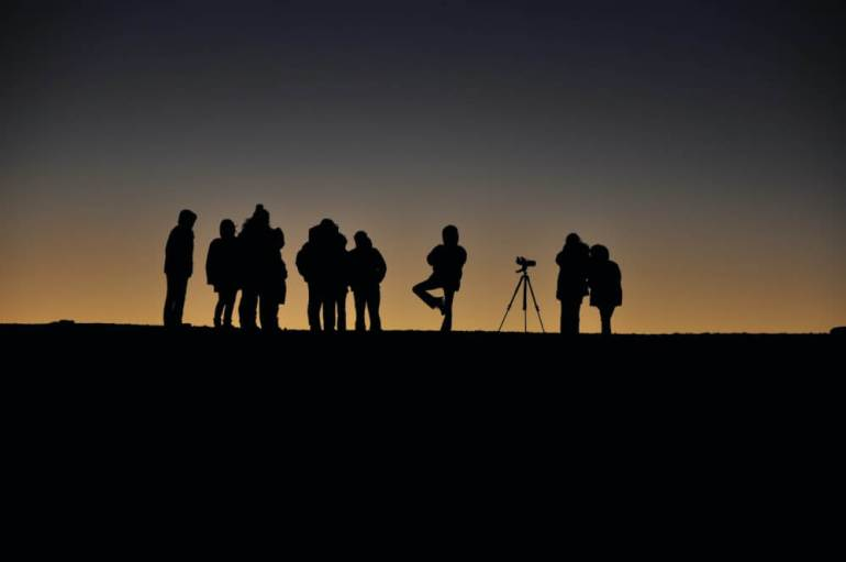Stargazing at Haleakala is a top thing to do on Maui. Image of the silhouette of a group of stargazers at Haleakala National Park.