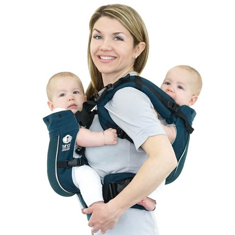 The TwinGo Air is one of the best baby carriers for hot weather. Image of a blond mom with two babies in a teal carrier.