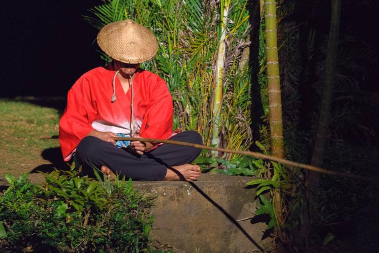 Image of a Japanese man sitting on a rock and fishing with a bamboo pole as part of the Kauai luau entertainment.