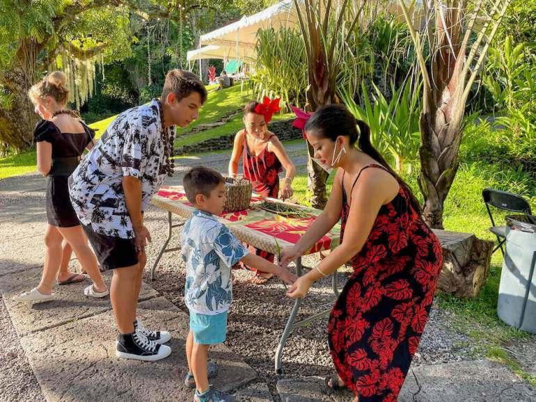 Get a ti leaf bracelet at the Nutridge Luau on Oahu. Image of a hula dancer putting a bracelet on a little boy.