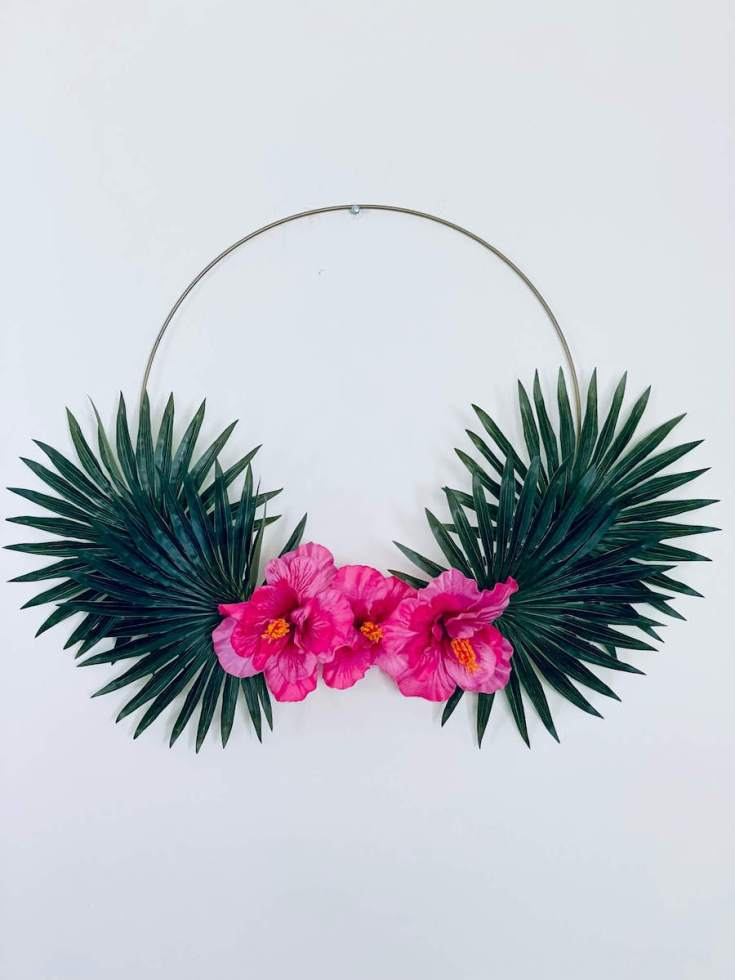 Image of a gold hoop wreath with palm leaves and pink hibiscus flowers on it.