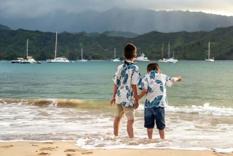 Your Kauai photographer will have lots of posing tips. Image of two boys holding hands facing the ocean on Kauai.