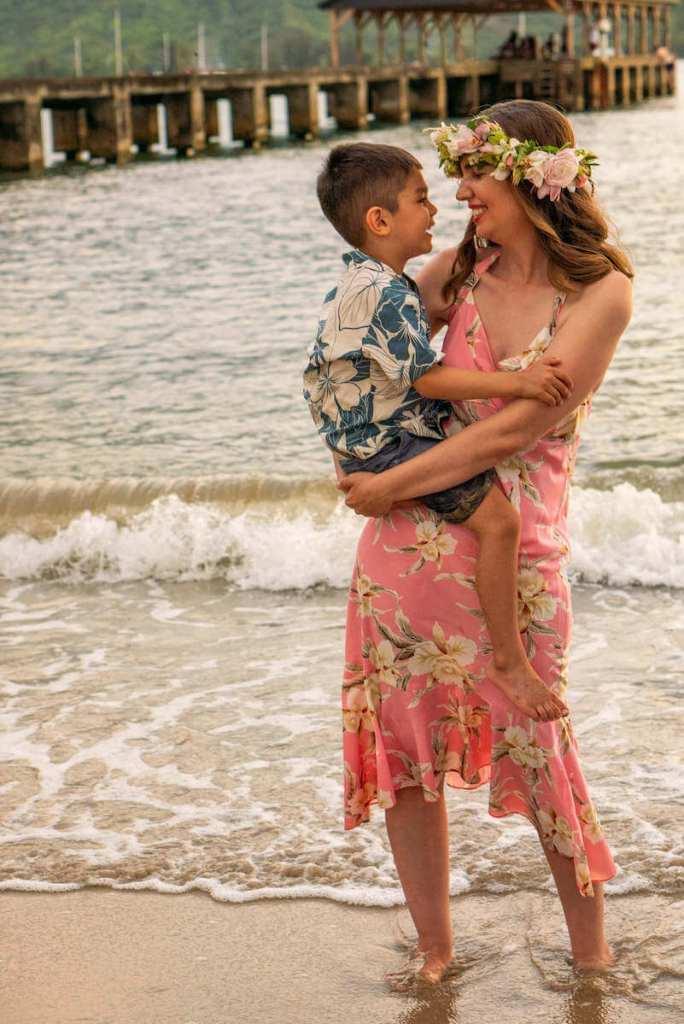 Image of a woman wearing a pink Hawaiian dress holding a boy wearing a blue Aloha shirt at Hanalei Pier on Kauai.