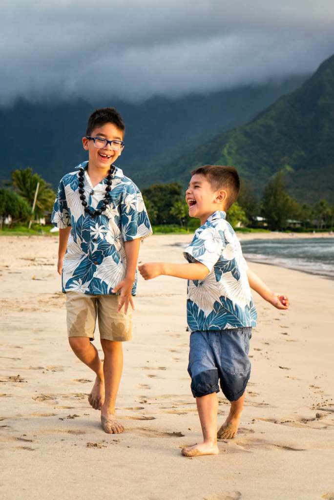 Get the cutest Hawaii family photography by booking a Flytographer photo shoot on Kauai. Image of two boys wearing Hawaiian shirts running on the beach laughing.