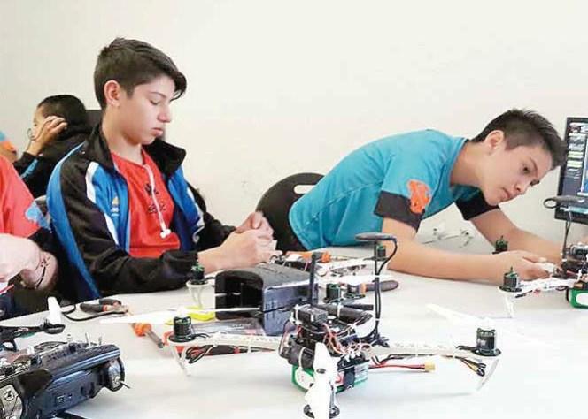 Chicos trabajando en un dron antibullying