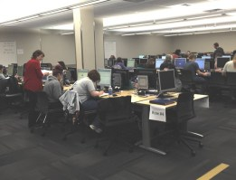 The picture shows a lab of about a hundred computers on several desks with students doing work.