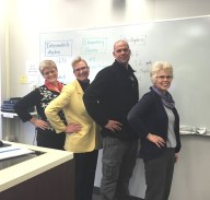 "Instructors standing in front of a classroom white board strike the ""Hawkes Pose"" by putting their hands on their hips."