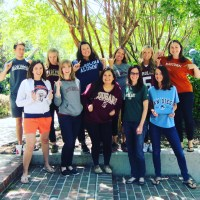 Eleven of Hawkes Learning's best and brightest employees stand outside wearing their college shirts. College names range from Eastern Connecticut State University to Notre Dame to University of San Diego to College of Charleston.