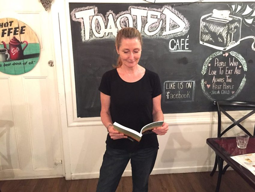 Toasted Cafe owner and author of Return to Tamarlin - K. M. Steele - enjoying the vibe reading at the debut Wild Readings Northside.
