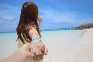 女性がビーチで手を引っ張っている様子