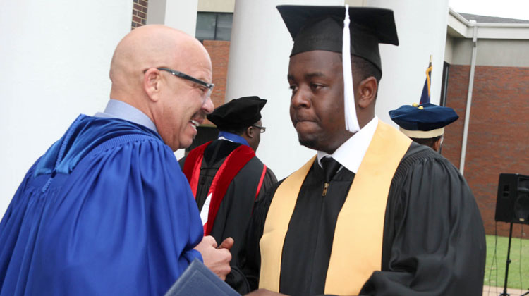 Tom Joyner congratulates a Stillman College graduate and Tom Joyner Scholarship recipient at his Commencement Ceremony.