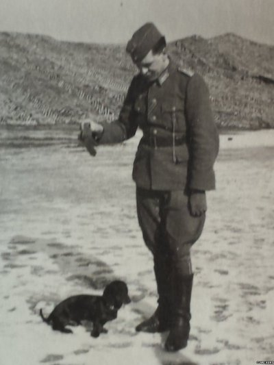 A German officer plays with a dachshund on a beach