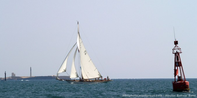Un bonito velero navega de entrada a la bahía. La boya y las construcciones sobre el horizonte enmarcan la fotografía.