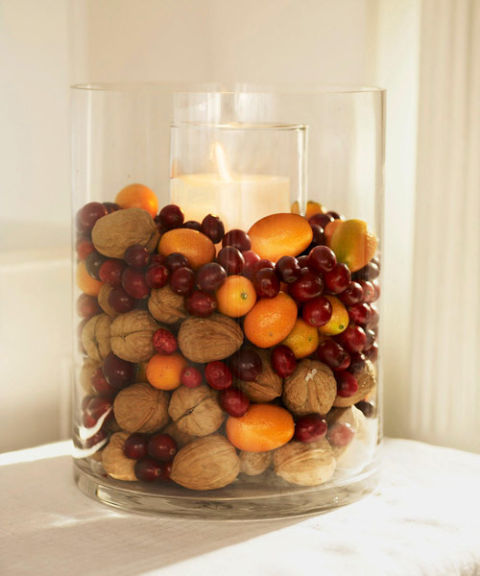 Display winter's most festive foods in a glass vase with a candle in the middle. This one has walnuts, cranberries, and kumquats. See more at Good Housekeeping »