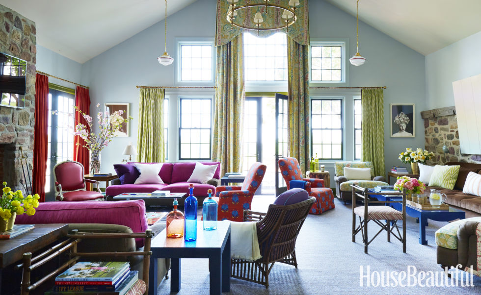 "In the new double-height living room, ""the eye gravitates to that fearless David Hicks flash of color — the fuchsia sofas that flank the fireplace,"" says designer Jeffrey Bilhuber. They're covered in Malabar's Tabia. A French armchair is upholstered in Designtex's Parga. The exuberant blue-and-persimmon print on a pair of chairs is Tulu's Stella. Another sofa, covered in a corduroy from Sonia's Place, is placed against the old exterior wall of the icehouse. Curtains in Osborne & Little's Serenissima in the center, Schumacher's Kasari Ikat at the sides, and Malabar's Carom at the left. Hanging Schoolhouse lights from Rejuvenation add a casual touch next to a two-tier Classic Ring chandelier from Circa Lighting. Walls in Woodlawn Blue and ceiling in Winds Breath, both by Benjamin Moore. Carpet by Patterson Flynn Martin."