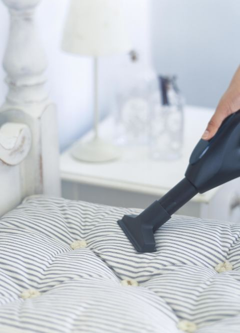 The perfect time to pay attention to what's under your bedding? When your sheets and comforter are being washed, too. Use your vacuum's crevice tool to clean the surface and sides, then spot-clean stains with an upholstery cleaners. Sanitize with a spritz of disinfectant spray afterwards and you're all set.