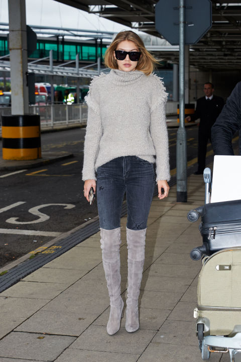 Arriving at London's Heathrow Airport in a gray turtleneck, jeans and suede over-the-knee boots.