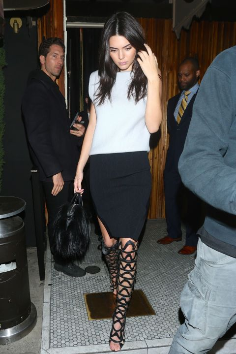 Leaving The Nice Guy in Los Angeles, wearing a white tank and black mini with a Givenchy goat hair bag and Sophia Webster over-the-knee gladiators.