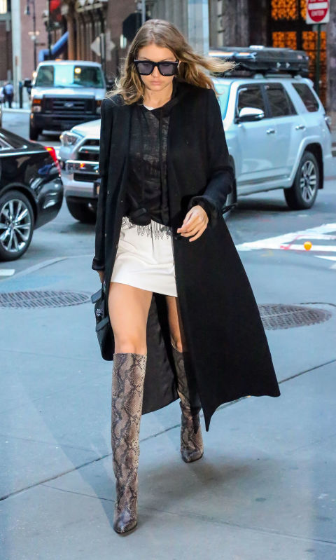 Out in NYC wearing a semi-sheer tee over a mini dress with a black duster jacket and knee-high snakeskin boots.