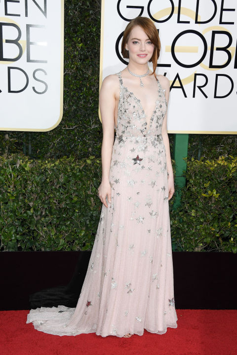 """Emma Stone took celestial motifs to new heights and cheekily nodded to LaLa Land's""""City of Stars"""" theme song at the 2017 Golden Globesin Valentino Haute Couture. The delicate pale ivories, nudes and metallics of her look weresubtle against her pale complexion, and paved the way for her stellar Tiffany & Co. collar to complement the look without appearing overdone. Get the Look: Valentino long dress in embroidered tulle, $7,160,valentino.com."""