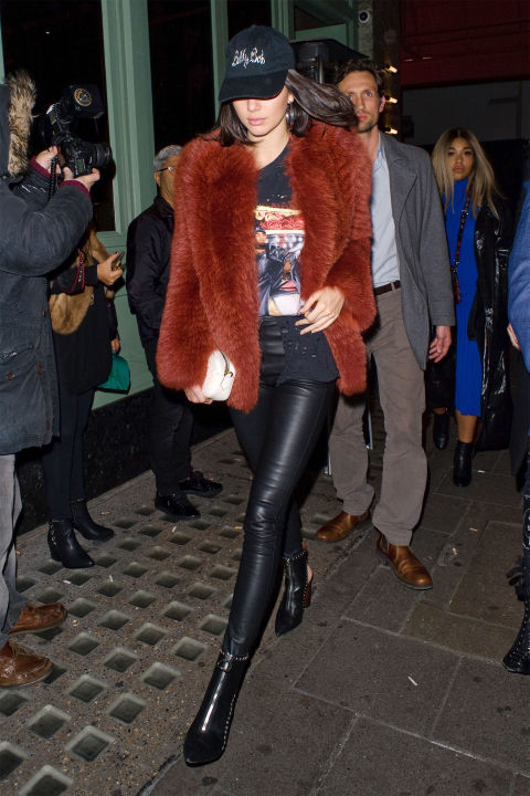 In a Zeynep Arçay fur jacket, graphic tee, leather leggings, studded Kurt Geiger ankle boots and dad hat while leaving SexyFish restaurant in London.