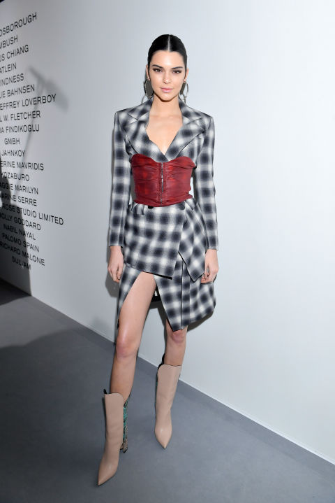 In a checked wrap dress wrapped with a red corset and beige leather pointed toe boots at the LVMH Prize cocktail reception in Paris.