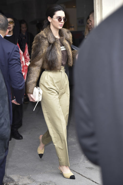 In a brown cropped fur coat, Supreme x Louis Vuitton t-shirt and high-waisted khaki pants with Chanel pumps and Krewe sunglasses while leaving the Chanel show in Paris.