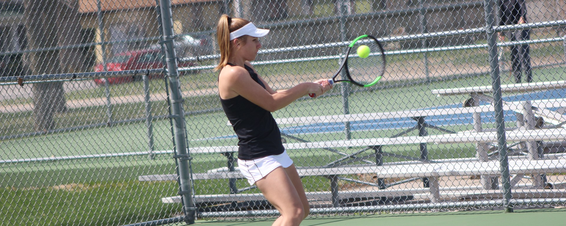 Senior Kelsey Brown keeps her eye on the ball to return it over the net in a match against Northwestern College. She defeated her opponent, keeping her undefeated record in GPAC play.