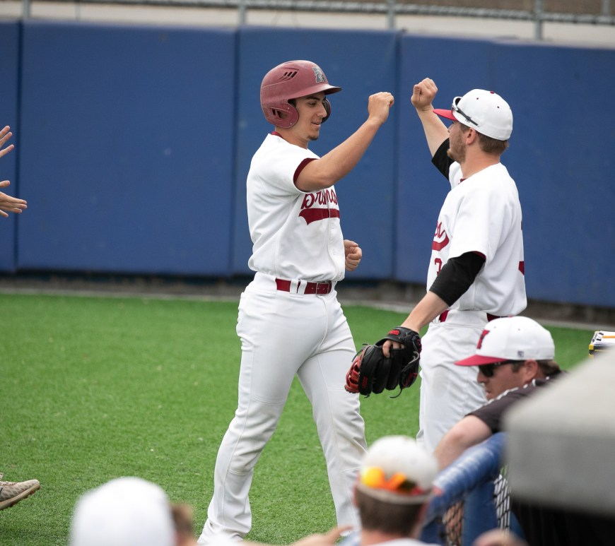 Junior Jayden Stack and Sophomore Ryder Ghidotti celebrate as the Broncos score their first run of the game against York College on April 9.