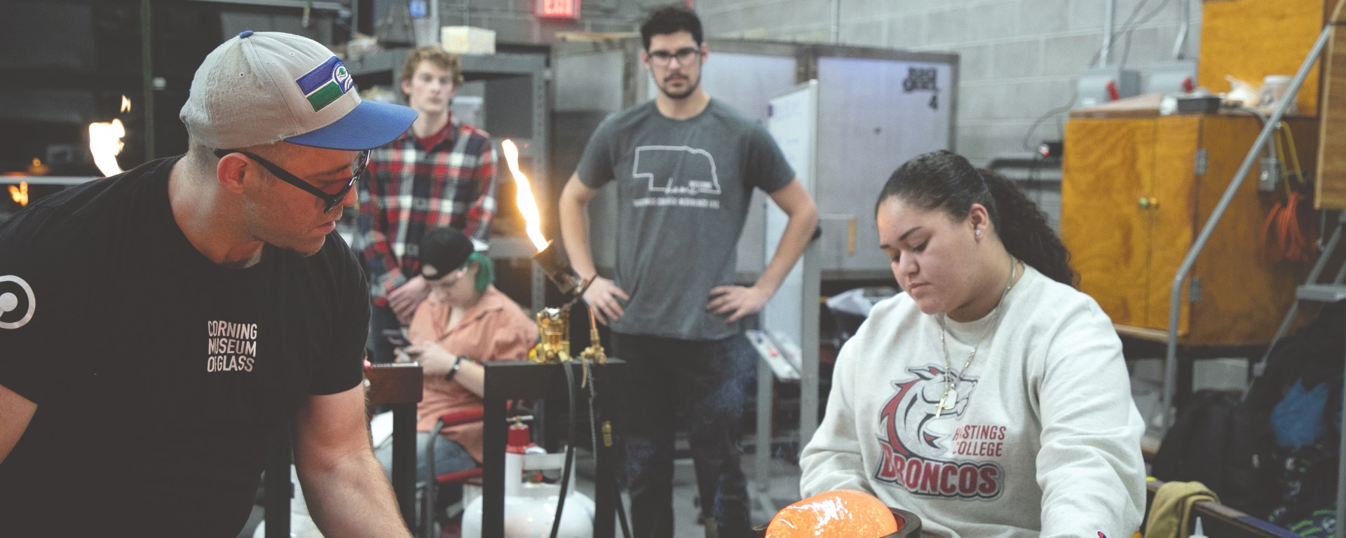Glass students aid in the process of blowing the piece.