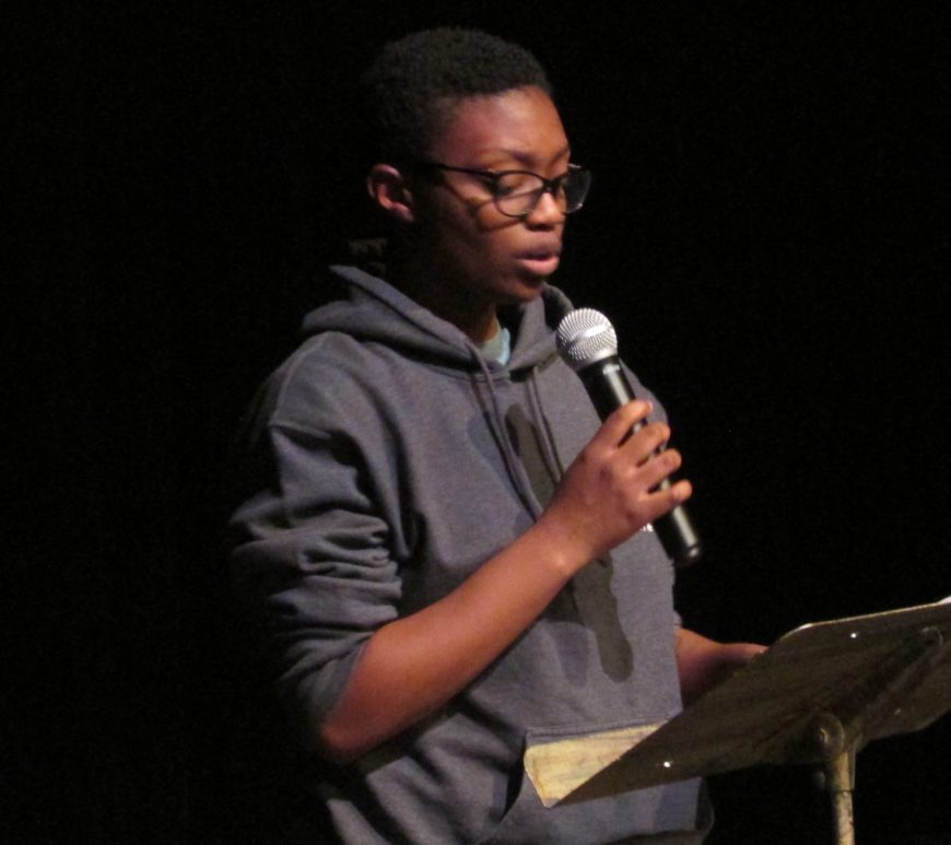 Sophomore Kai Marshall performs their original poem for the audience at the poetry open mic event.