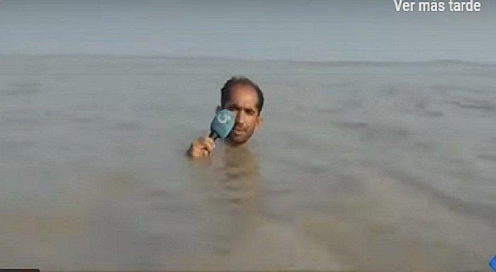 Un reportero paquistaní habla a la cámara con el agua al cuello