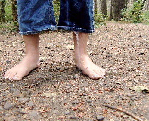 A stream of pee pours out of the bottom of Olivia's pants leg as she wets herself.