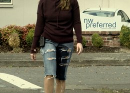 Close-up of Alisha peeing in her jeans while walking along a busy city street.