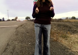 Alisha pees in her jeans while standing alongside a country highway.